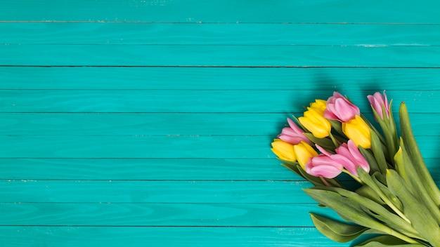 黄色の平面図。緑の木製の机の上のピンクのチューリップの花