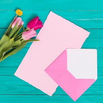 白紙の高角度のビュー。木製の背景上の封筒とチューリップの花を開く