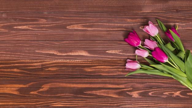 木製のテーブルにピンクのチューリップの花のオーバーヘッドビュー