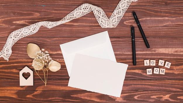 Вид сверху кружева; чистый лист; форма сердца; деревянная ручка на деревянной поверхности