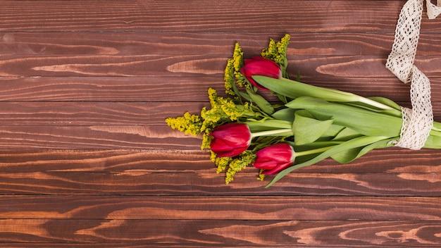 Букет из красных тюльпанов и золотарника, перевязанный кружевом на деревянном фоне
