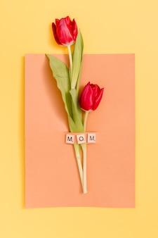 黄色の背景上の母の日グリーティングカードと赤いチューリップの花の上から見る