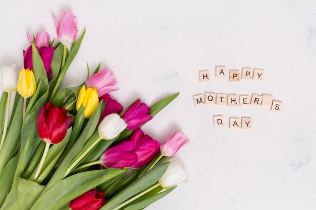 白いコンクリートの背景に色とりどりのチューリップの花と幸せな母の日のテキスト