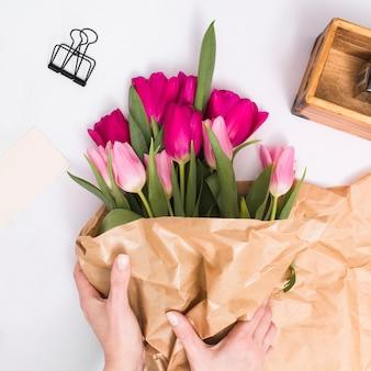 白い背景で隔離の上の茶色の紙とチューリップの花の花束を作る人の手
