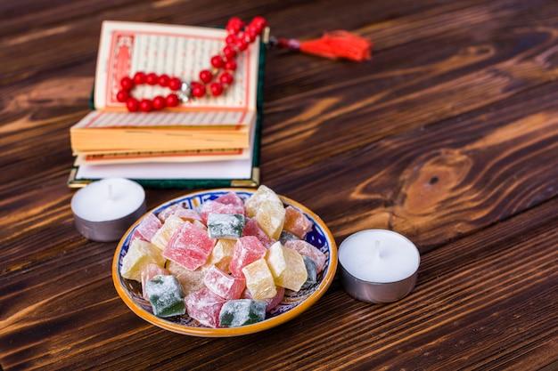 Разноцветные кубики рахат-лукум в тарелке с священной книгой ислама; четки и свечи на деревянный стол