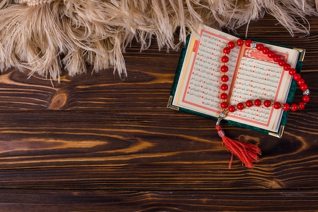 木製の机の上のイスラムの神聖な本と祈りビーズの俯瞰