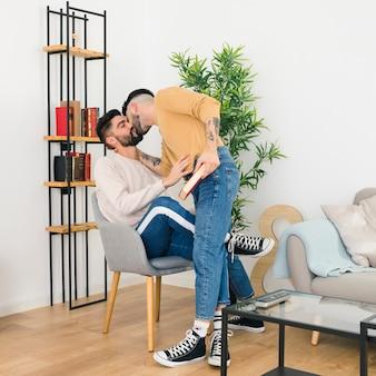 男がリビングルームの椅子に座って彼のボーイフレンドにキス