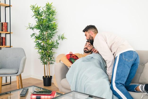 若い男がソファで寝ている彼氏によって運ばれる彼の赤ちゃんを見て