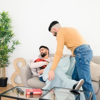 リビングルームのソファーに赤ちゃんと一緒に寝ている彼氏の上に青い毛布を置く男のクローズアップ