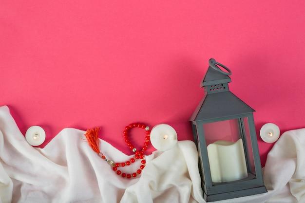 赤い祈りビーズと赤い背景の上の白い布の上の火をつけたキャンドルキャンドルホルダー