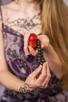 赤の禅ボールとビーズのブレスレットを持つ女性の手