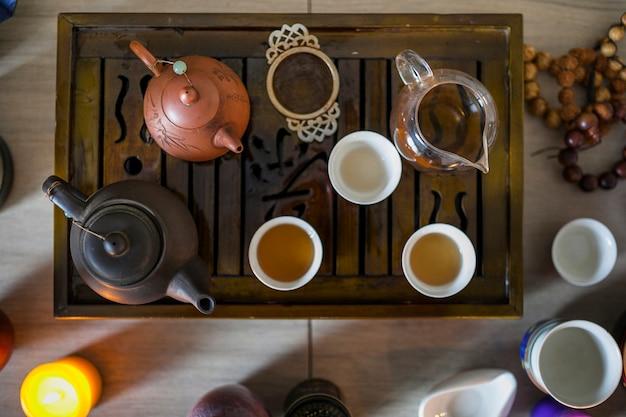 火のともったろうそくが付いている木の皿にお茶セットの俯瞰