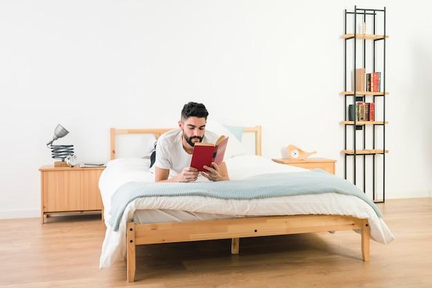 Мужчина лежит на кровати и читает книгу в спальне