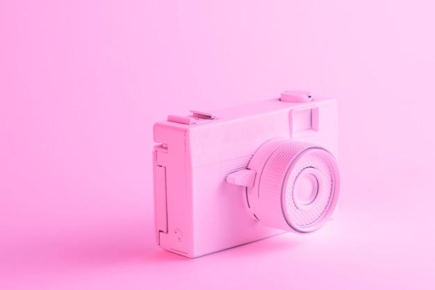 ピンクの背景に対して塗られたカメラのクローズアップ