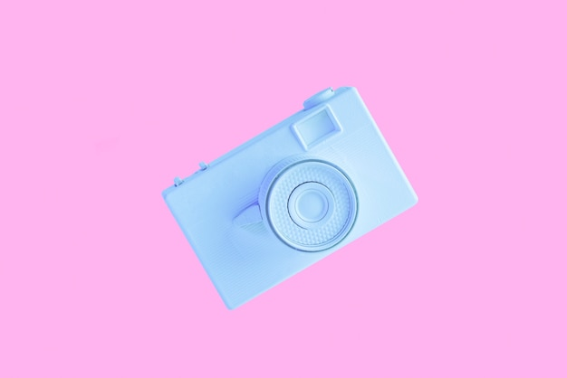 ピンクの背景に対して空気中の青い塗られたカメラ