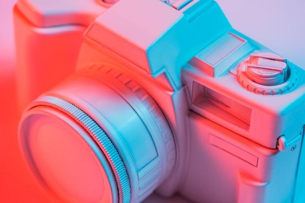 青い光とレトロなピンクのカメラのクローズアップ