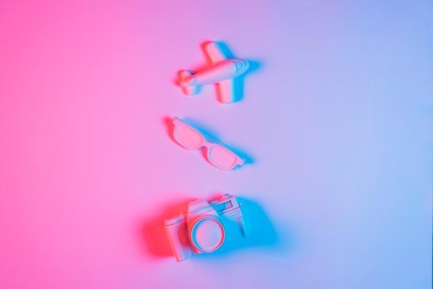 ミニチュア飛行機。ピンクの背景の上の眼鏡とレトロなカメラ