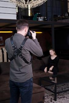 カメラマンがソファの上のモデルの写真を撮る