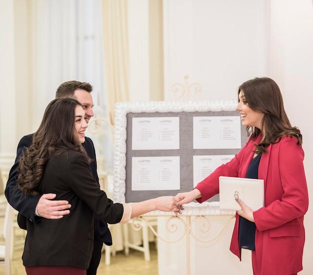 若いカップルと握手のイベントマネージャー