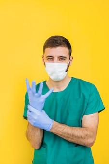 Мужской доктор в маске надевает стерильные перчатки