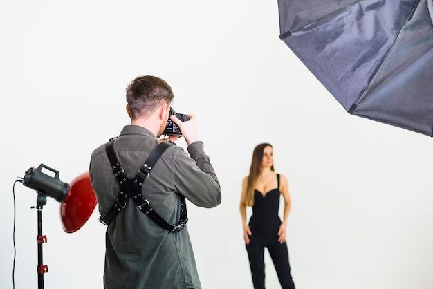 スタジオでモデルの写真を撮る写真家