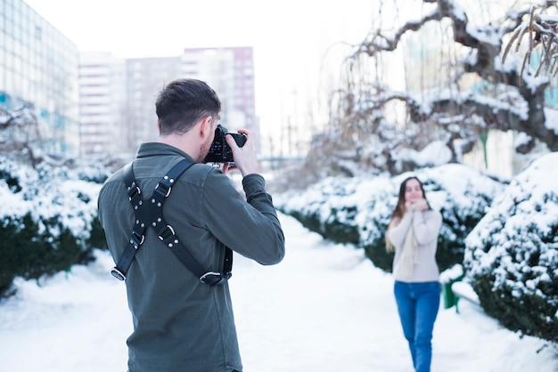 雪に覆われた通りでモデルの写真を撮る写真家