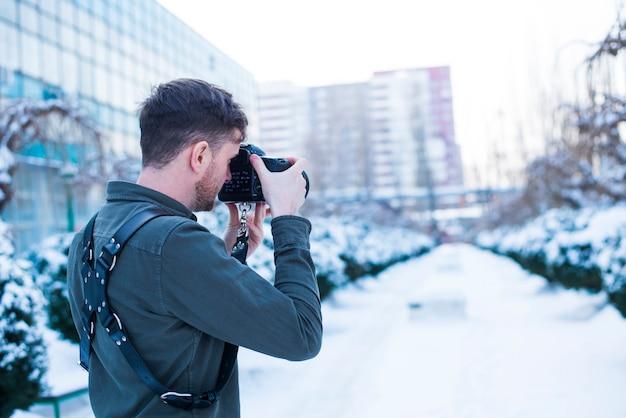 雪に覆われた通りの写真を撮る男性カメラマン