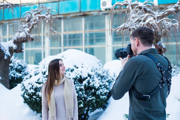 雪に覆われた通りで女性モデルの写真を撮る写真家
