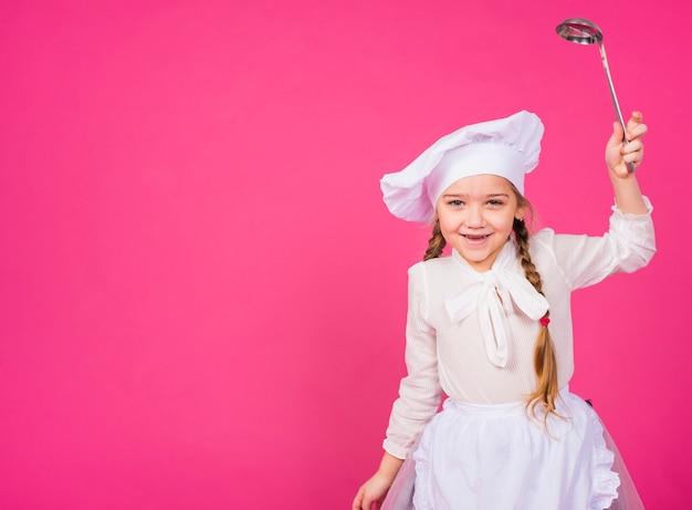 お玉を笑顔で調理する少女
