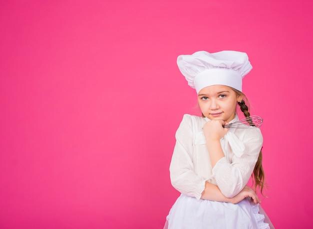 思いやりのある少女は泡立て器で料理します
