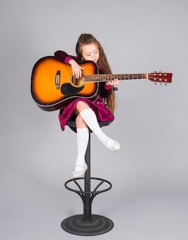 小さな女の子がバーの椅子にアコースティックギターを弾く
