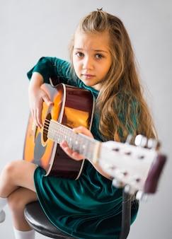 Маленькая девочка в платье играет на акустической гитаре