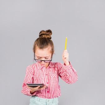 Девушка в очках с ручкой с помощью планшета