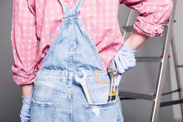 Женщина с гаечным ключом в заднем кармане джинсовый комбинезон