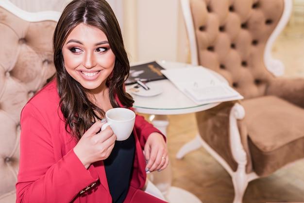 きれいな女性が肘掛け椅子でコーヒーを飲む