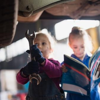 スパナと雑誌で立っているオーバーオールの二人の少女