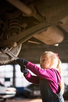 Маленькая девочка в общем ремонтирует автомобиль с гаечным ключом