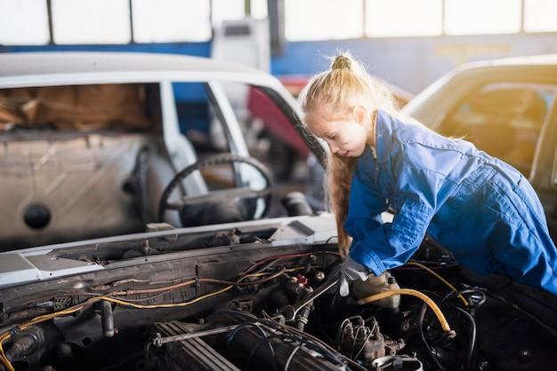 Маленькая девочка ремонтирует автомобиль с помощью гаечного ключа