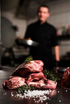Стейки из сырого мяса с ингредиентами на столе