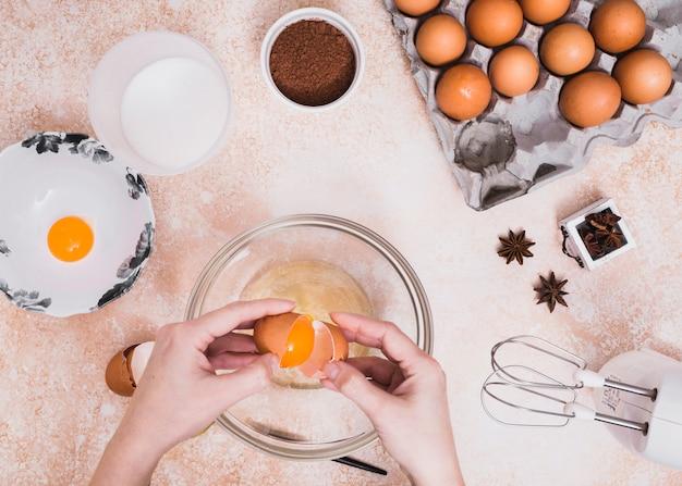 ケーキ生地を作るためのガラスのボウルに卵を割る人のクローズアップ