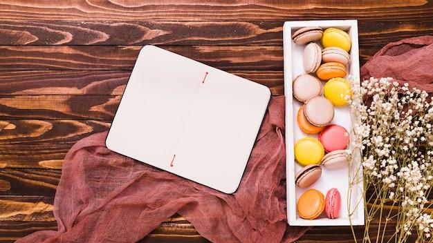 空白のスパイラルメモ帳。マカロン白い木製の箱と背景の上のリネンの石膏