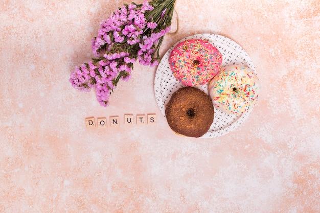 Фиолетовые цветы гипсофилы; блоки пончики и запеченные пончики на тарелке на деревенском фоне
