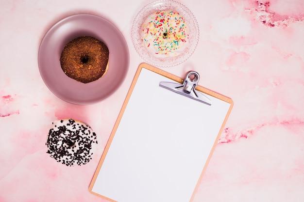 織り目加工の背景上のクリップボードにホワイトペーパーとチョコレートと白のドーナツ