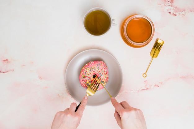 織り目加工の背景に対してフォークとバターナイフでピンクのドーナツを切る女性の手のクローズアップ