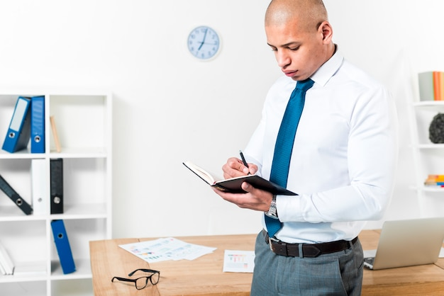 ペンで日記に書くテーブルの前に立っている実業家のクローズアップ