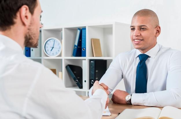 Улыбаясь портрет молодого бизнесмена рукопожатие с его партнером-мужчиной