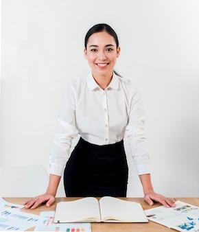 白い壁に対して机の後ろに立っている若い実業家の笑みを浮かべて肖像画