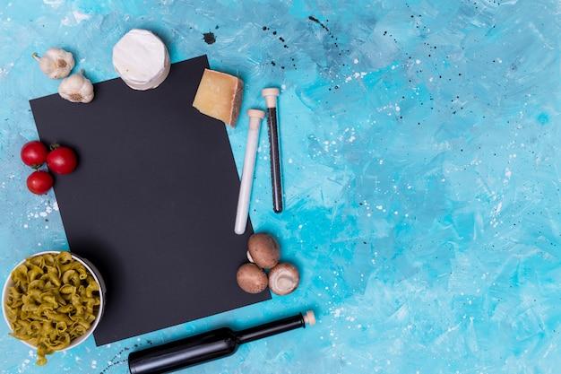 新鮮なベジタリアン食材と青い表面上の黒いスレートと未調理のパスタのオーバーヘッドビュー