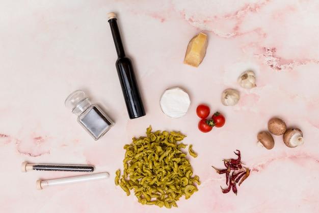 様々な食材に囲まれた生のイタリアパスタのクローズアップ
