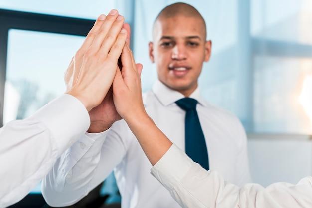 彼のビジネスパートナーにハイタッチを与えるビジネスマンのクローズアップ